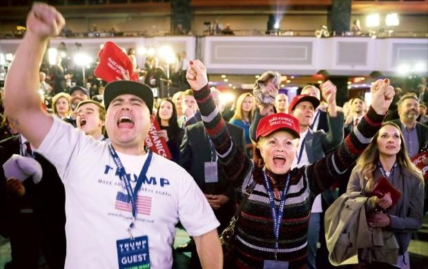 """< """"이겼다"""" > '미국을 다시 위대하게'라는 구호가 적힌 모자를 쓴 도널드 트럼프 미국 대통령 당선자의 지지자들이 8일(현지시간) 뉴욕 힐튼미드타운호텔 로비에 모여 트럼프 당선을 축하하며 환호하고 있다. 뉴욕AFP연합뉴스"""