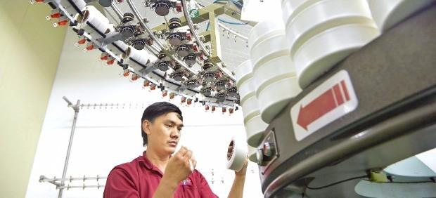 효성 베트남 공장에서 현지 직원이 스판덱스 품질을 검사하고 있다.