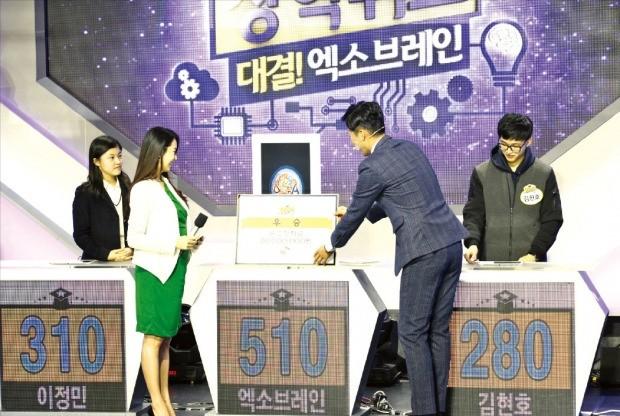 지난 18일 대전에서 열린 EBS 장학퀴즈 프로그램에서 사회자가 우승을 차지한 한국형 인공지능 엑소브레인에 우승 상금을 전달하고 있다. ETRI 제공