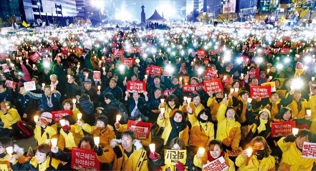 """< 광화문 밝힌 LED 촛불 > 지난 19일 서울 광화문광장 일대에서 촛불집회 참가자들이 """"박근혜 퇴진""""을 외치면서 촛불을 밝히고 있다. 상당수는 꺼지지 않는 'LED(발광다이오드) 촛불'을 들고 나왔다. 주최 측은 서울 부산 광주 등 전국 각지에서 동시에 열린 4차 촛불집회에 총 95만명(경찰 추산 26만명)이 참가했다고 추산했다. 허문찬 기자 sweat@hankyung.com"""