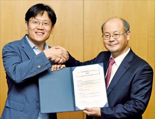 황현수 포도트리 사업총괄이사(왼쪽)와 이학영 한국경제신문 기획조정실장이 22일 '2017 한경 신춘문예 협력 양해각서(MOU)'에 사인한 뒤 악수하고 있다. 허문찬 기자 sweat@hankyung.com