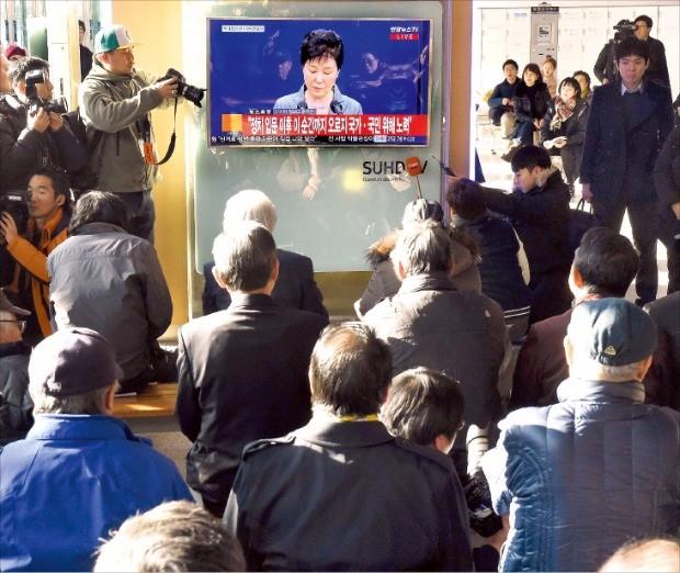 시민들이 29일 서울역에서 박근혜 대통령의 3차 대국민 담화를 TV로 지켜보고 있다. 김영우 기자 youngwoo@hankyung.com