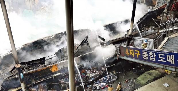 """< 연말 앞두고 """"장사 어쩌나"""" > 소방관들이 30일 대구 대신동 서문시장에서 화재를 진압하고 있다. 이날 화재로 서문시장 6개 지구 상가 중 한 곳인 4지구 상가 점포 679곳이 모두 불에 타고 건물 일부가 무너져내렸다. 연합뉴스"""