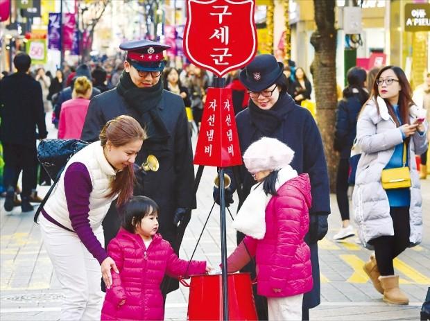 자선냄비에 사랑을 담으세요 ♣♣한 모녀가 1일 서울 명동 거리에 마련된 구세군 자선 냄비에 기부금을 넣고 있다. 구세군은 이날부터 오는 31일까지 한 달간 모금 활동을 한다.  허문찬 기자 ♣♣sweat@hankyung.com