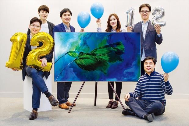 삼성전자 영상디스플레이사업부 직원들이 QLED(양자점 발광다이오드) TV로 올해까지 12년 연속 세계시장 점유율 1위를 달성하겠다는 의지를 다지며 숫자 '12' 모양의 풍선을 들고 있다.