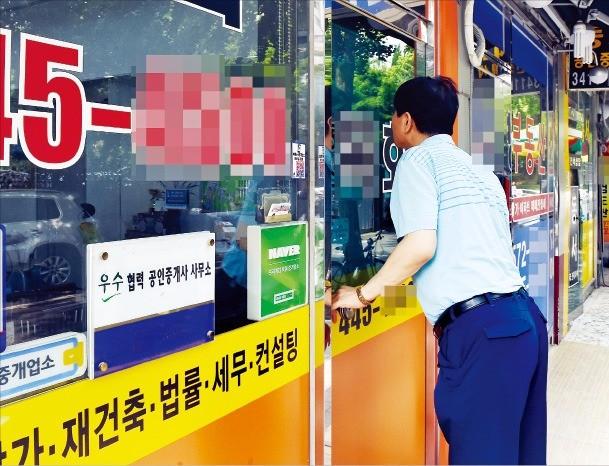 정부가 부동산 대책을 발표한 19일 한 시민이 서울 개포동 공인중개업소 안을 들여다보고 있다. 이 일대 중개업소 대부분은 정부 단속 소식에 지난주부터 문을 닫고 잠정 휴업에 들어갔다. 허문찬 기자 sweat@hankyung.com