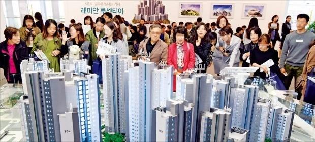 서울 운니동 래미안갤러리에서 13일 개장한 '래미안 DMC루센티아(가재울뉴타운 5구역)' 아파트 모델하우스에서 예비 청약자들이 단지 모형을 둘러보고 있다. 김영우 기자 youngwoo@hankyung.com