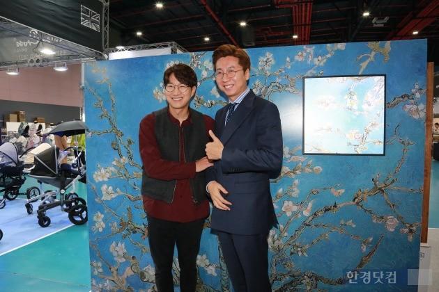 이원영 블루캔버스 대표가 서울베이비페어를 찾은 조우종 아나운서와 사진을 찍어 액자로 옮기는 장면을 재현하기 위해 촬영중이다.