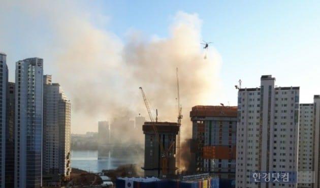 경기 수원시 광교신도시의 아파트 공사현장에서 25일 화재가 발생했다. 소방헬기가 동원돼 진화를 벌이고 있다. (사진 독자제공)