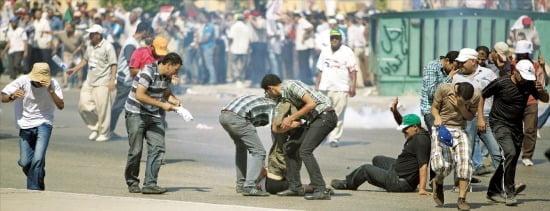 < 軍발포…무르시지지자최소3명사망> 무함마드무르시전이집트대통령지지자들이5일카이로시내에서군이발포한총에맞은동료들을옮기고있다.외신들은최소3명이숨졌다고전했다./기자AP연합뉴스