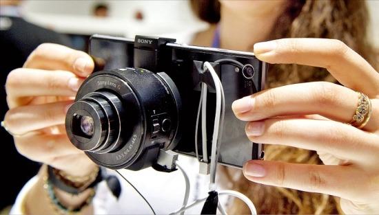 IFA에서 소니는 신개념 카메라 'QX10, QX100'을 공개했다. 카메라본체는 렌즈 역할만 하고 카메라 조작부와 LCD 화면은 스마트폰, 태블릿으로 대체할 수 있는 방식이다. 한 관람객이 QX100에 소니의 스마트폰 '엑스페리아'를 결합해 사용하고 있다. 연합뉴스