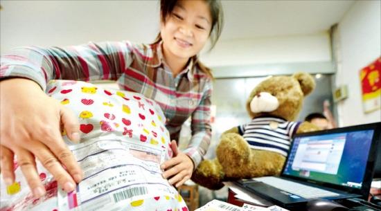 중국 장쑤성 양저우시의 한 온라인 쇼핑몰 상인이 지난 10일 고객에게 배송될 상품에 배송장을 붙이고 있다. '광군제'엔 대부분의 온라인 쇼핑몰에서 상품을 50% 할인 판매한다. 양저우신화연합뉴스