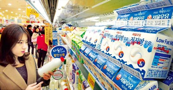 < 유통기한 언제까지? > 우유는 소비자들이 유통기한에 민감한 품목이어서 유통기한이 지나면 부패 여부에 관계없이 대부분 버려진다. 한 소비자가 지난 21일 서울의 한 대형마트에서 우유 유통기한을 확인하고 있다. 허문찬 기자 sweat@hankyung.com