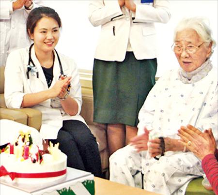 지난해 대장암 수술을 마친 문귀춘 할머니(오른쪽·수술 당시 102세)가 의료진, 가족들과 함께 축하 파티를 열고 있다. 문 할머니는 54명의 자손을 두고 있다. 서울성모병원 제공