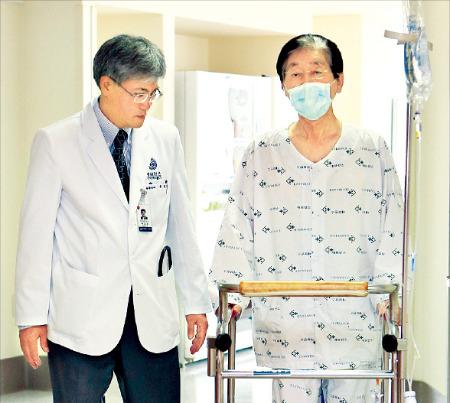 백효채 연세대 세브란스병원 흉부외과 교수(왼쪽)가 국내 최고령 폐 이식수술을 받고 회복 중인 남모씨(71)의 재활 훈련을 지켜보고 있다. 세브란스병원 제공