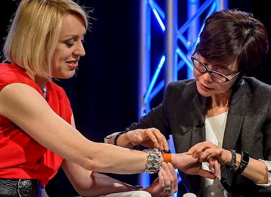 이영희 삼성전자 부사장이 MWC 2014에서 사샤 트위닝(Sasha Twining) 앵커(왼쪽) 손목에  '삼성 기어2'를 직접 채워주고 있다.