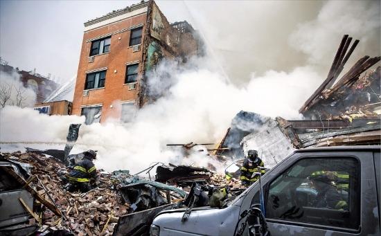 미국 뉴욕 맨해튼 이스트 할렘에서 12일 오전 9시30분께(현지시간) 폭발로 붕괴된 아파트 잔해에서 연기가 치솟고 있다. 뉴욕AP연합뉴스