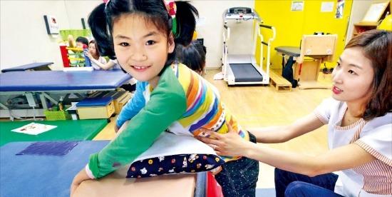 뇌병변 1급 장애아인 김소정 양(10·왼쪽)이 7일 서울 신교동 푸르메재활센터에서 물리치료사로부터 재활 치료를 받고 있다. 정동헌 기자 dhchung@hankyung.com