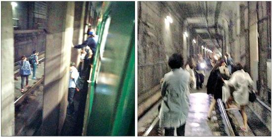 < 탈출하는 승객들 > 2일 오후 서울메트로 2호선 상왕십리역에서 잠실 방향으로 가던 열차가 정지해 있던 앞 열차와 추돌하는 사고가 발생하자 승객들이 열차 문을 직접 열고 나와 어두운 철로를 따라 대피하고 있다. 트위터