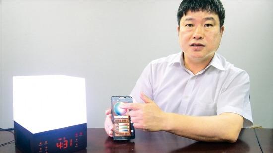 오진근 티엔엔솔루션 대표가 '스마트LED큐브'의 색상을 스마트폰으로 선택하는 방법에 대해 설명하고 있다. 추가영 기자