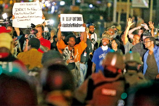 """< 분노한 시위대 > 10대 흑인청년 마이클 브라운이 백인 경찰관의 총격으로 숨진 미국 미주리주 퍼거슨시에서 18일(현지시간) 시위대가 행진을 막는 경찰에 """"손을 들었다. 쏘지 말라""""는 구호를 외치며 격렬하게 항의하고 있다. 경찰은 이날 밤 시위대를 향해 수차례 해산 명령을 내린 끝에 최루탄과 연막탄 등을 쐈다. 퍼거슨AP연합뉴스"""