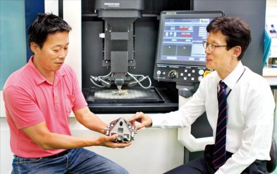 서정훈 인스텍 사장(오른쪽)이 박주노 부사장과 3D 금속프린터로 만든 제품에 대해 얘기하고 있다. 김낙훈 기자