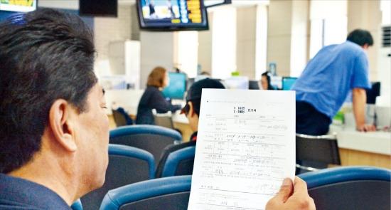 < 마포세무서 하루 100여건 폐업신고 > 지난 19일 오후 폐업 신고를 하기 위해 서울 마포세무서 민원봉사실을 찾은 민원인이 관련 서류를 작성한 뒤 차례를 기다리고 있다. 마포세무서에서만 하루 평균 100여건의 폐업신고가 접수된다. 김병언 기자 misaeon@hankyung.com