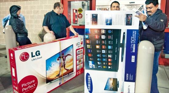 27일(현지시간) 오후 시작된 블랙 프라이데이 행사에서 특별 세일 제품으로 판매된 대형 TV를 구매한 소비자가 밝은 표정으로 매장을 나오고 있다. 페어팩스AFP연합뉴스