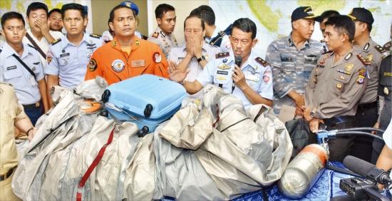 < 가방 주인은 어디에… > 인도네시아 공군 수색대장(앞줄 오른쪽 두 번째)이 30일 보르네오섬 팡칼란분 공군기지에서 기자회견을 열고 지난 28일 해상으로 추락한 에어아시아 여객기(QZ8501)에서 수거한 유실물에 대해 설명하고 있다. 팡칼란분AP연합뉴스