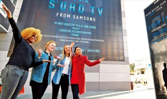 < CES 6일 개막 > 미국 라스베이거스에서 6일 개막하는 세계 최대 가전전시회 'CES 2015'를 앞두고 삼성전자가 행사장 앞에 설치한 'SUHD TV'(퀀텀닷을 적용한 초고화질 TV) 옥외광고물 앞에서 전시담당 직원들이 활짝 웃고 있다. 삼성전자 제공