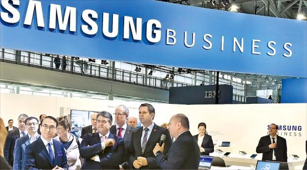 홍원표 삼성전자 최고마케팅책임자( 사장·앞줄 맨 왼쪽)가 16일(현지시간) 독일 하노버에서 열린 정보통신 박람회 '세빗 2015'에서 삼성전자 전시장을 돌아보고 있다. 삼성전자는 '삼성 비즈니스'를 첫 B2B 브랜드로 내걸었다. 삼성전자 제공