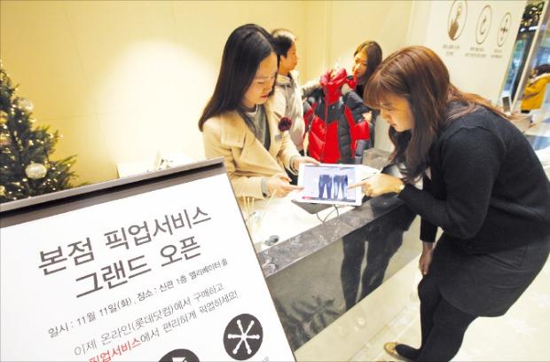 한 소비자(오른쪽)가 온라인으로 주문한 상품을 서울 소공동 롯데백화점 본점에 설치돼 있는 온라인 픽업서비스 전용데스크에서 찾아가기 위해 확인하고 있다.