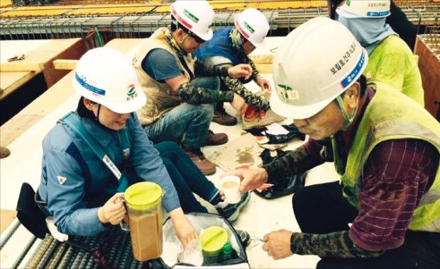 GS건설 본사 직원이 서울의 한 아파트 건설현장에서 더위에 지친 직원들에게 음료수를 나눠주고 있다.
