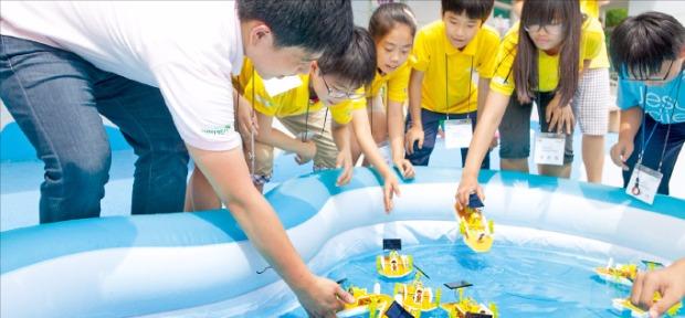 LS드림사이언스클래스에 참가한 직원과 지역 아동들이 태양전지보트 과학키트를 제작해 시연하고 있다.