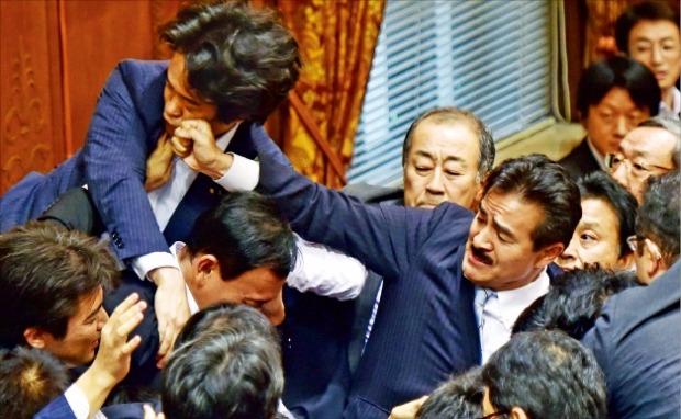 일본 자유민주당의 사토 마사히사 참의원(오른쪽)이 17일 의회에서 열린 참의원 평화안전법제 특별위원회 회의에서 법안 표결에 항의하는 민주당의 고니시 히로유키 참의원의 얼굴을 주먹으로 치고 있다. 도쿄EPA연합뉴스