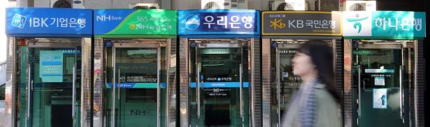 (서울=연합뉴스) 최재구 기자 = 주거래 은행 계좌를 손쉽게 옮길 수 있는 계좌이동제 시행을 하루 앞둔 29일 서울시내에 설치된 은행별 ATM기 앞을 시민들이 지나고 있다.