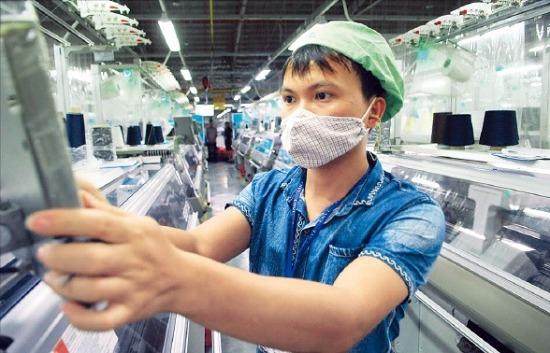 < 하이퐁의 의류공장 > 베트남 북부 하이퐁에 있는 의류공장에서 한 근로자가 기계를 살피고 있다. 하이퐁VNA연합뉴스