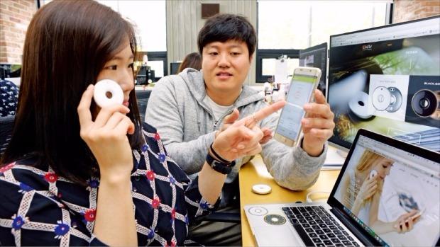 문종수 웨이웨어러블 대표(오른쪽)가 피부상태 측정 기기인 웨이로 한 직원의 얼굴을 검사한 결과를 스마트폰 앱을 통해 보여주고 있다. 신경훈 기자 nicerpeter@hankyung.com