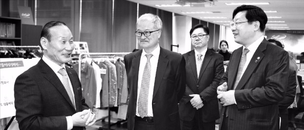 최병오 패션그룹형지 회장(왼쪽)이 26일 회사를 방문한 주형환 산업통상자원부 장관(오른쪽)과 성기학 섬유산업연합회장(영원무역 회장·왼쪽 두 번째)에게 중국 진출 현황을 설명하고 있다. 산업통상자원부 제공