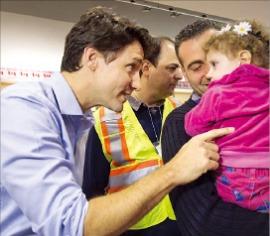 """< 1978년 그리고 2015년…난민에게 관대한 캐나다 > 저스틴 트루도 캐나다 총리(왼쪽)가 지난해 12월11일 캐나다 토론토 피어슨국제공항에 내린 시리아 난민 소녀에게 """"집에 온 것을 환영한다""""고 말하고 있다. 토론토AP연합뉴스"""