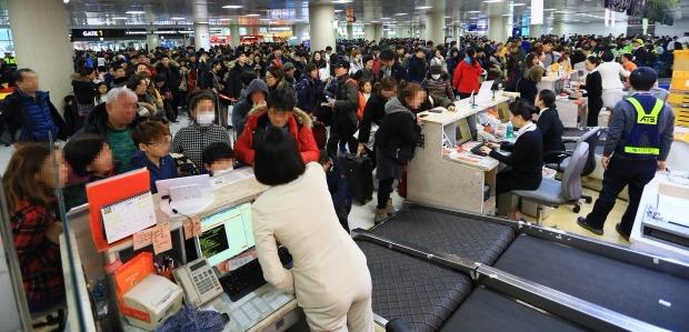 <  다시 시작된 '집에 가기' 전쟁 >  26일 오전 제주공항 국내선 창구가 대기·수속 승객으로 붐비고 있다.연합뉴스