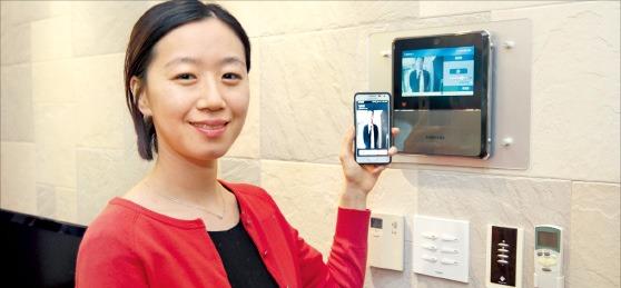 삼성SDS의 홈시큐리티 솔루션에 가입한 한 고객이 스마트폰으로 방문자를 확인할 수 있는 모바일 영상통화 기능을 시연하고 있다. 삼성SDS 제공