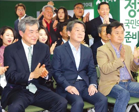안철수 상임공동대표(앞줄 가운데)를 비롯한 국민의당 관계자들이 13일 서울 마포 당사에서 방송 3사 출구조사 결과를 지켜보고 있다. 연합뉴스