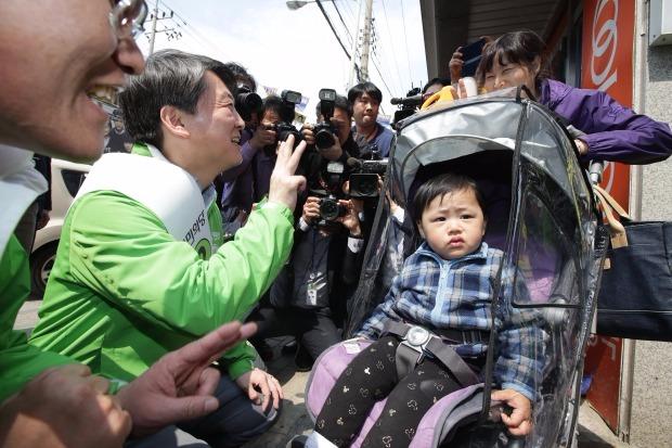 국민의당 안철수 공동대표가 5일 오후 의정부시 제일시장에서 의정부갑에 출마한 김경호 후보의 지원유세를 하다가 한 어린이의 나이를 묻고 있다.