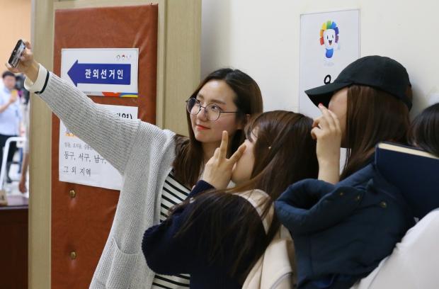 (광주=연합뉴스) 김도훈 기자 = 제20대 총선 사전투표가 시작된 8일 오후 광주시 북구청 투표소에서 투표를 마친 학생들이 인증사진을 찍고 있다.