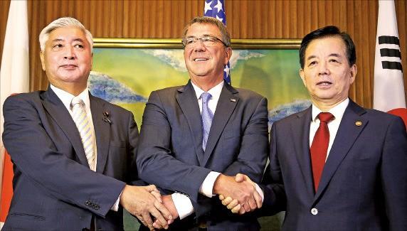 제15차 아시아안보회의(샹그릴라 대화)에 참석한 한민구 국방부 장관(오른쪽)이 지난 4일 싱가포르 샹그릴라호텔에서 애슈턴 카터 미국 국방장관(가운데), 나카타니 겐 일본 방위상과 회담에 앞서 손을 잡고 있다. 싱가포르AP연합뉴스