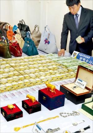 경찰이 11일 현금과 명품가방, 시계, 금송아지 등 압수품을 공개하고 있다. 연합뉴스