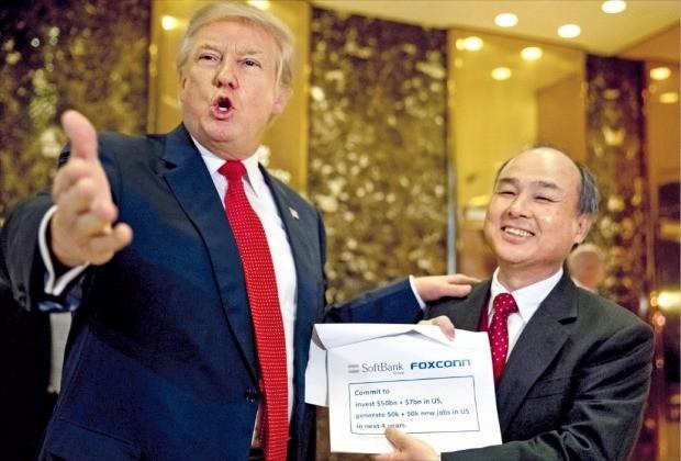 """< """"투자 환영합니다"""" >  손정의 일본 소프트뱅크 사장(오른쪽)이 6일(현지시간) 뉴욕 트럼프타워 로비에서 도널드 트럼프 미국 대통령 당선자와 함께 500억 달러(약 58조원) 투자계획서를 펼쳐보이고 있다. 뉴욕AP연합뉴스"""