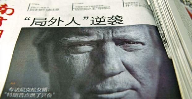 """< 트럼프의 '역습' > 환구시보를 비롯한 중국 관영 언론들이 12일 도널드 트럼프 미국 대통령 당선자에게 """"'하나의 중국' 정책은 결코 흥정할 수 있는 대상이 아니다""""고 목소리를 높였다. 지난달 10일 '아웃사이더의 역습'이란 제목으로 트럼프의 대통령 당선 소식을 전한 베이징의 한 신문. 베이징AFP연합뉴스"""