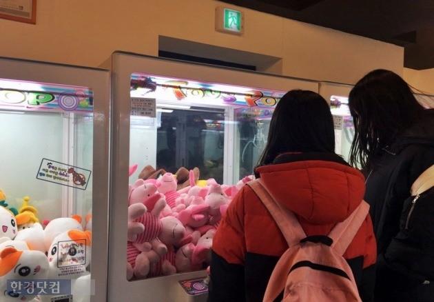 지난 10일 서울 신촌의 인형뽑기방에서 청소년들이 기계 속 인형을 들여다보고 있다.